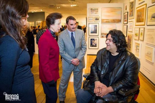 Afshin talks to guests at his exhibition